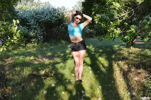 First-rate chica in a blue midriff shirt and black shorts flashing her boobs under a tree. - XXXonXXX - Pic 1