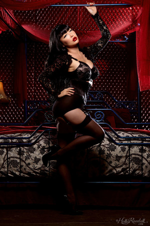 Luscious Asian babe displays her erotic body in all black lingerie, nighty, stockings with suspenders and high heels then she takes off her bra and expose her big round boobs before she removes her panty and bares her sexy booty while she lays down seductively on a red, white and gray bed. - XXXonXXX - Pic 1