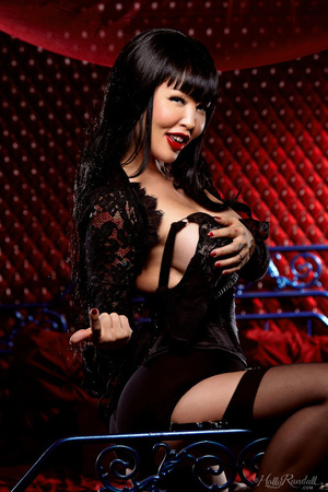 Luscious Asian babe displays her erotic body in all black lingerie, nighty, stockings with suspenders and high heels then she takes off her bra and expose her big round boobs before she removes her panty and bares her sexy booty while she lays down seductively on a red, white and gray bed. - XXXonXXX - Pic 4