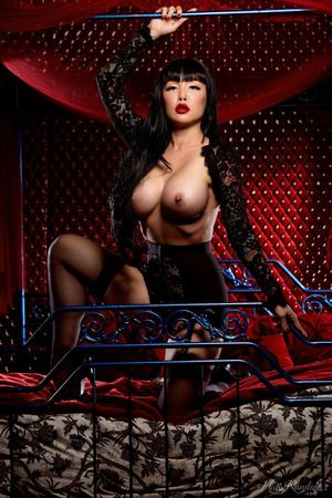 Luscious Asian babe displays her erotic body in all black lingerie, nighty, stockings with suspenders and high heels then she takes off her bra and expose her big round boobs before she removes her panty and bares her sexy booty while she lays down seductively on a red, white and gray bed. - XXXonXXX - Pic 6