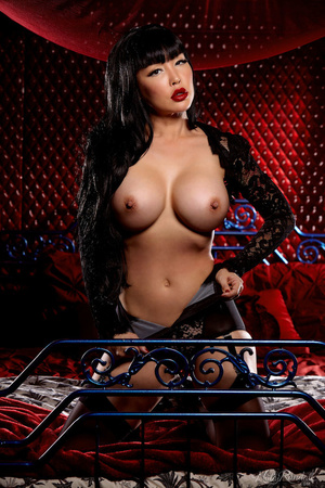 Luscious Asian babe displays her erotic body in all black lingerie, nighty, stockings with suspenders and high heels then she takes off her bra and expose her big round boobs before she removes her panty and bares her sexy booty while she lays down seductively on a red, white and gray bed. - XXXonXXX - Pic 9