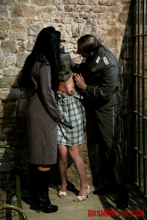 Gagged blonde in a plaid dress gets inspected by some uniformed guards. - XXXonXXX - Pic 1