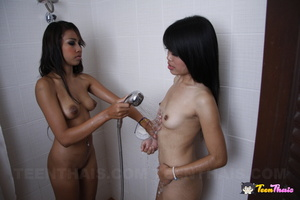 Naked Asian babe gets her sexy body wet while taking a shower then she rubs soap in her ass before she lets another hot Thai join her then she gives her a shower before they make out in the bathroom. - XXXonXXX - Pic 9