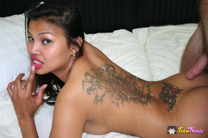 Sexy Thai takes off her silver dress and expose her hot breasts and tattooed pussy in string of pink flower shaped beads then she lets a white dude lick her pussy before she sucks his cock on a white bed. - XXXonXXX - Pic 15