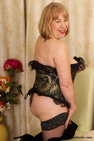 Mature blonde wearing gold and blue corset, black stockings and boots shows her huge breasts then rubs her nasty pussy on a couch. - XXXonXXX - Pic 1