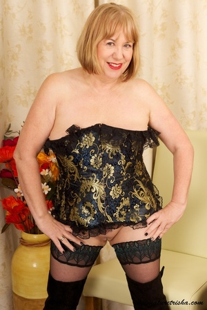 Mature blonde wearing gold and blue corset, black stockings and boots shows her huge breasts then rubs her nasty pussy on a couch. - XXXonXXX - Pic 2