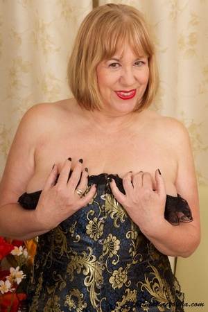 Mature blonde wearing gold and blue corset, black stockings and boots shows her huge breasts then rubs her nasty pussy on a couch. - XXXonXXX - Pic 4