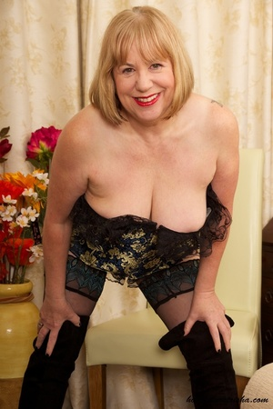 Mature blonde wearing gold and blue corset, black stockings and boots shows her huge breasts then rubs her nasty pussy on a couch. - XXXonXXX - Pic 5