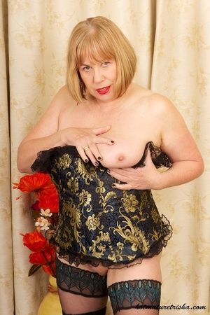 Mature blonde wearing gold and blue corset, black stockings and boots shows her huge breasts then rubs her nasty pussy on a couch. - XXXonXXX - Pic 7
