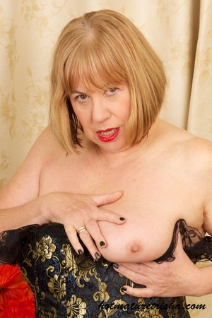 Mature blonde wearing gold and blue corset, black stockings and boots shows her huge breasts then rubs her nasty pussy on a couch. - XXXonXXX - Pic 8