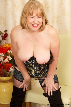 Mature blonde wearing gold and blue corset, black stockings and boots shows her huge breasts then rubs her nasty pussy on a couch. - XXXonXXX - Pic 9