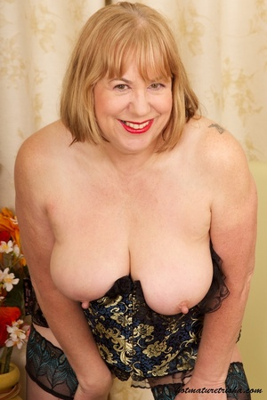 Mature blonde wearing gold and blue corset, black stockings and boots shows her huge breasts then rubs her nasty pussy on a couch. - XXXonXXX - Pic 10