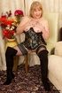 Mature blonde wearing gold and blue corset, black stockings and boots