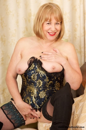 Mature blonde wearing gold and blue corset, black stockings and boots shows her huge breasts then rubs her nasty pussy on a couch. - XXXonXXX - Pic 14