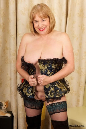 Mature blonde wearing gold and blue corset, black stockings and boots shows her huge breasts then rubs her nasty pussy on a couch. - XXXonXXX - Pic 15