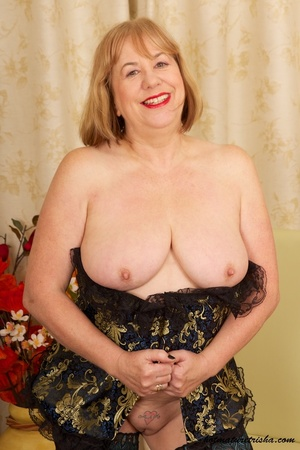 Mature blonde wearing gold and blue corset, black stockings and boots shows her huge breasts then rubs her nasty pussy on a couch. - XXXonXXX - Pic 16