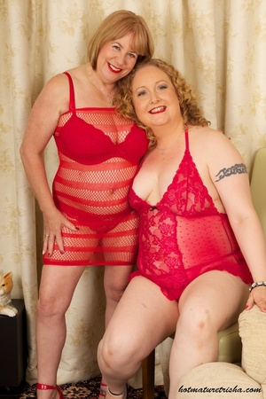 Two mature blondes in red lingerie licks each others old breasts on a white and brown chair. - XXXonXXX - Pic 3