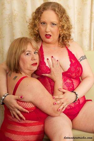 Two mature blondes in red lingerie licks each others old breasts on a white and brown chair. - XXXonXXX - Pic 5