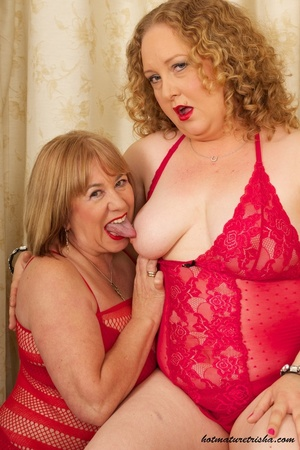 Two mature blondes in red lingerie licks each others old breasts on a white and brown chair. - XXXonXXX - Pic 6
