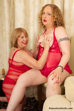 Two mature blondes in red lingerie licks each others old breasts on a white and brown chair. - XXXonXXX - Pic 8