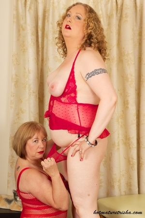 Two mature blondes in red lingerie licks each others old breasts on a white and brown chair. - XXXonXXX - Pic 10
