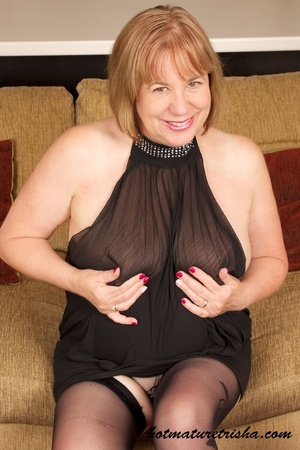 Busty old babe expose her huge breasts under her black dress then takes it off and shows her fat body before she pulls down her red and black panty and rubs her pussy wearing her black stockings and high heels on a brown couch. - XXXonXXX - Pic 1