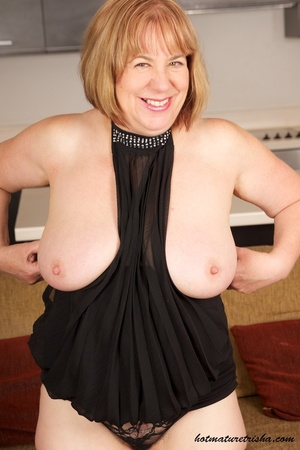 Busty old babe expose her huge breasts under her black dress then takes it off and shows her fat body before she pulls down her red and black panty and rubs her pussy wearing her black stockings and high heels on a brown couch. - XXXonXXX - Pic 4