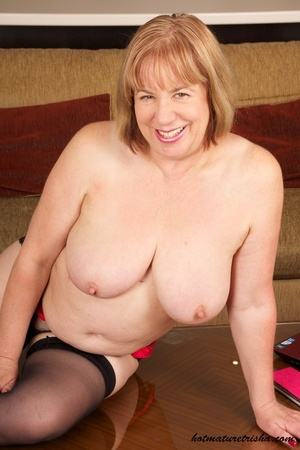Busty old babe expose her huge breasts under her black dress then takes it off and shows her fat body before she pulls down her red and black panty and rubs her pussy wearing her black stockings and high heels on a brown couch. - XXXonXXX - Pic 9
