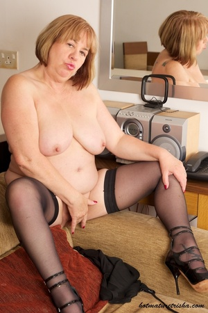 Busty old babe expose her huge breasts under her black dress then takes it off and shows her fat body before she pulls down her red and black panty and rubs her pussy wearing her black stockings and high heels on a brown couch. - XXXonXXX - Pic 15