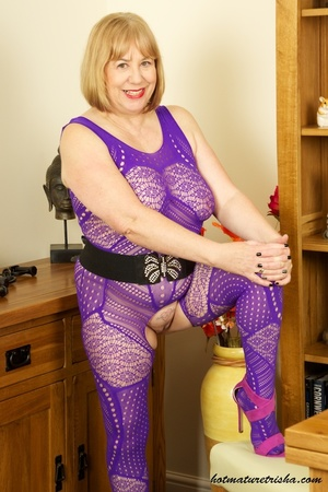 Mature blonde wearing purple outfit takes off the bra of her fat girlfriend wearing blue underwear with blue and red hearts, black stockings and high heels then licks her huge tits. - XXXonXXX - Pic 1