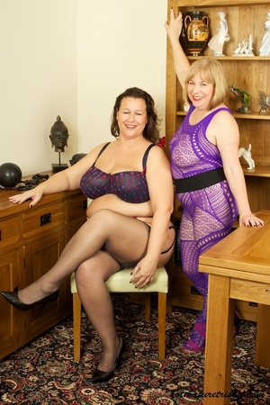 Mature blonde wearing purple outfit takes off the bra of her fat girlfriend wearing blue underwear with blue and red hearts, black stockings and high heels then licks her huge tits. - XXXonXXX - Pic 3