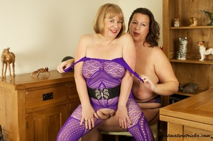 Mature blonde wearing purple outfit takes off the bra of her fat girlfriend wearing blue underwear with blue and red hearts, black stockings and high heels then licks her huge tits. - XXXonXXX - Pic 15