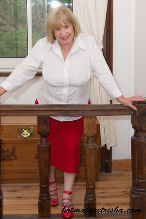 Old blonde chick takes off her white blouse then bares her mature breasts before she strips down her red skirt and displays her huge butt wearing her red high heels by the window. - XXXonXXX - Pic 6