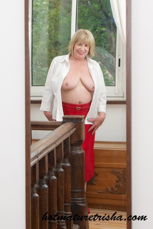 Old blonde chick takes off her white blouse then bares her mature breasts before she strips down her red skirt and displays her huge butt wearing her red high heels by the window. - XXXonXXX - Pic 9