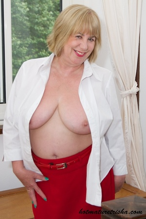 Old blonde chick takes off her white blouse then bares her mature breasts before she strips down her red skirt and displays her huge butt wearing her red high heels by the window. - XXXonXXX - Pic 10