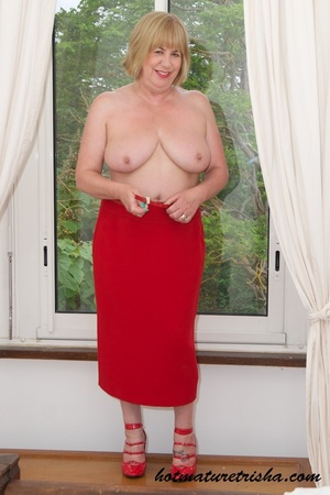 Old blonde chick takes off her white blouse then bares her mature breasts before she strips down her red skirt and displays her huge butt wearing her red high heels by the window. - XXXonXXX - Pic 12