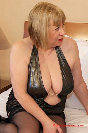 Hot mature babe wearing black nighty, stockings and high heels licks the big boobs of a cute fat chick in blue nighty before they display their big breasts as they pose on an orange and maroon stripe bed. - XXXonXXX - Pic 4