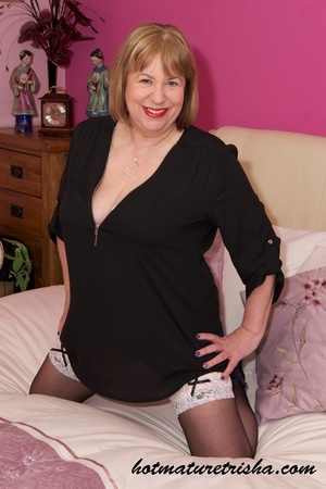 Old blonde chick takes off her black blouse and pose her big body in black and blue underwear, black stockings and blue high heels before she peels off her bra and release her big tits on a pink bed. - XXXonXXX - Pic 1