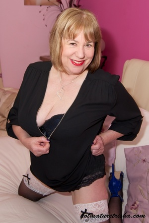 Old blonde chick takes off her black blouse and pose her big body in black and blue underwear, black stockings and blue high heels before she peels off her bra and release her big tits on a pink bed. - XXXonXXX - Pic 3