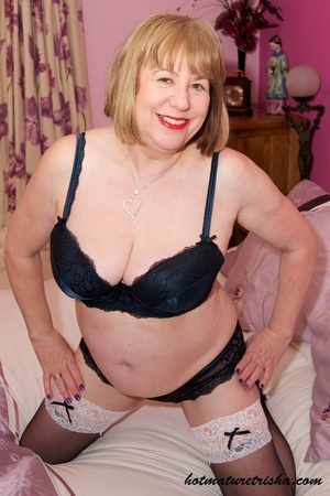 Old blonde chick takes off her black blouse and pose her big body in black and blue underwear, black stockings and blue high heels before she peels off her bra and release her big tits on a pink bed. - XXXonXXX - Pic 7