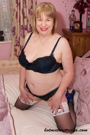 Old blonde chick takes off her black blouse and pose her big body in black and blue underwear, black stockings and blue high heels before she peels off her bra and release her big tits on a pink bed. - XXXonXXX - Pic 8