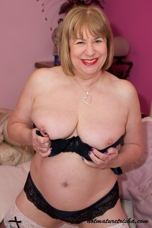 Old blonde chick takes off her black blouse and pose her big body in black and blue underwear, black stockings and blue high heels before she peels off her bra and release her big tits on a pink bed. - XXXonXXX - Pic 11