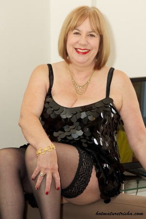 Fat mature chick in her hot black dress takes it off and pose wearing black lingerie, stockings and high heels before she removes her bra and expose her huge juggs on a brown couch. - XXXonXXX - Pic 4