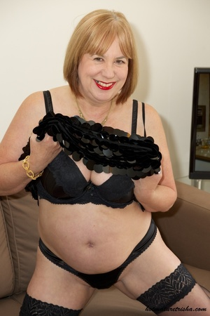 Fat mature chick in her hot black dress takes it off and pose wearing black lingerie, stockings and high heels before she removes her bra and expose her huge juggs on a brown couch. - XXXonXXX - Pic 9