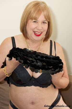 Fat mature chick in her hot black dress takes it off and pose wearing black lingerie, stockings and high heels before she removes her bra and expose her huge juggs on a brown couch. - XXXonXXX - Pic 10