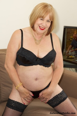 Fat mature chick in her hot black dress takes it off and pose wearing black lingerie, stockings and high heels before she removes her bra and expose her huge juggs on a brown couch. - XXXonXXX - Pic 11