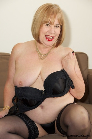 Fat mature chick in her hot black dress takes it off and pose wearing black lingerie, stockings and high heels before she removes her bra and expose her huge juggs on a brown couch. - XXXonXXX - Pic 13