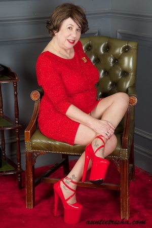 Mature brunette takes off her red dress then displays her big body in red nighty, high heels and brown stockings before she exposes her huge breasts then rubs her pussy on a green chair. - XXXonXXX - Pic 4
