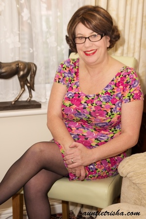 Mature chick with glasses strips off her colorful floral dress then pose her huge body in violet and black underwear, black stockings and purple high heels before she takes off her bra and expose her huge boobs on a brown couch. - XXXonXXX - Pic 1