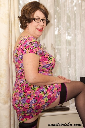Mature chick with glasses strips off her colorful floral dress then pose her huge body in violet and black underwear, black stockings and purple high heels before she takes off her bra and expose her huge boobs on a brown couch. - XXXonXXX - Pic 4